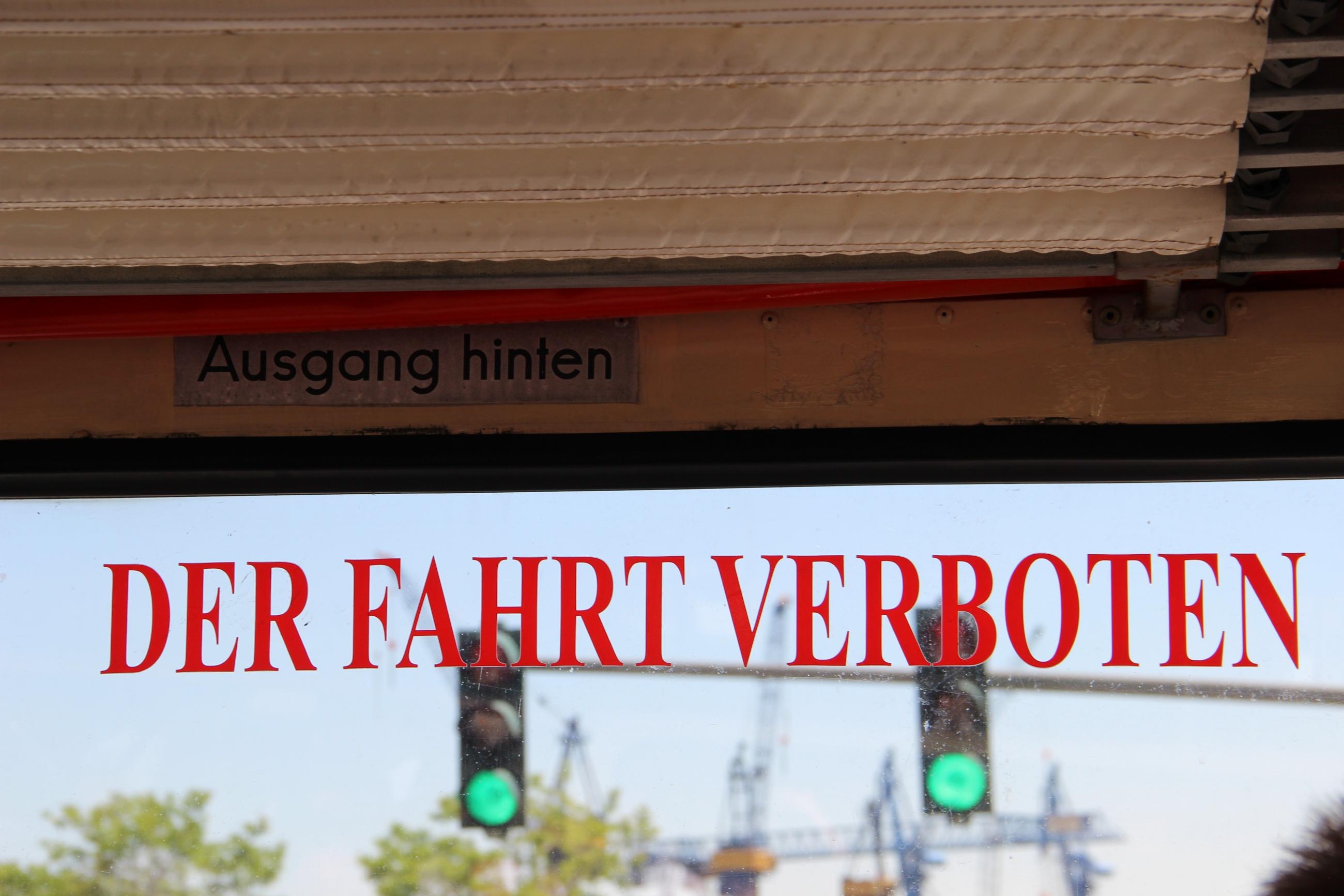 Foto: Blick aus dem Fenster auf einen Hafenkran. Auf dem Fenster ist in roter Blockschrift: 'Der Fahrt verboten' zu lesen.