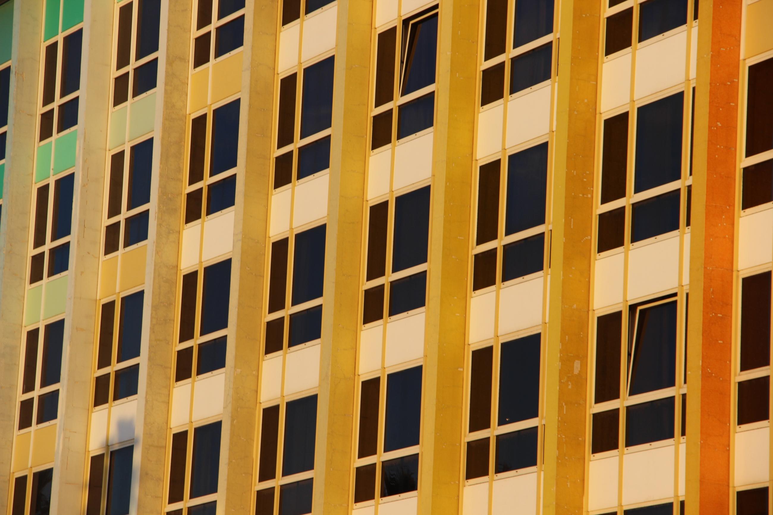 Foto: Freundliche Häuserfassade mit dunklen, streng angeordneten Fenstern