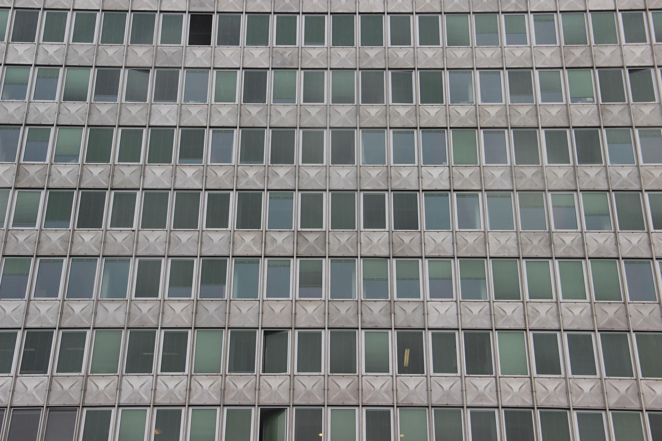 Foto: Graue moderne Fassade mit dunklen Fenstern. Hinter manchen brennt schwaches Neonlicht.