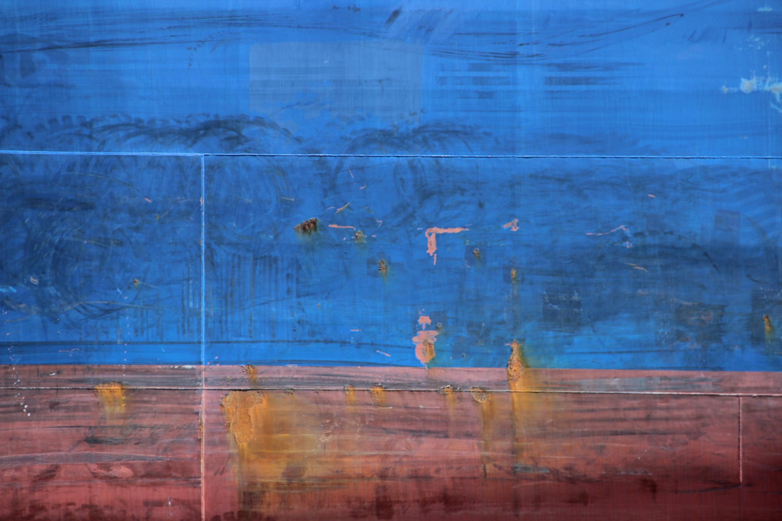 Foto: Blau und rot bemalter Schiffsrumpf mit Rostflecken.