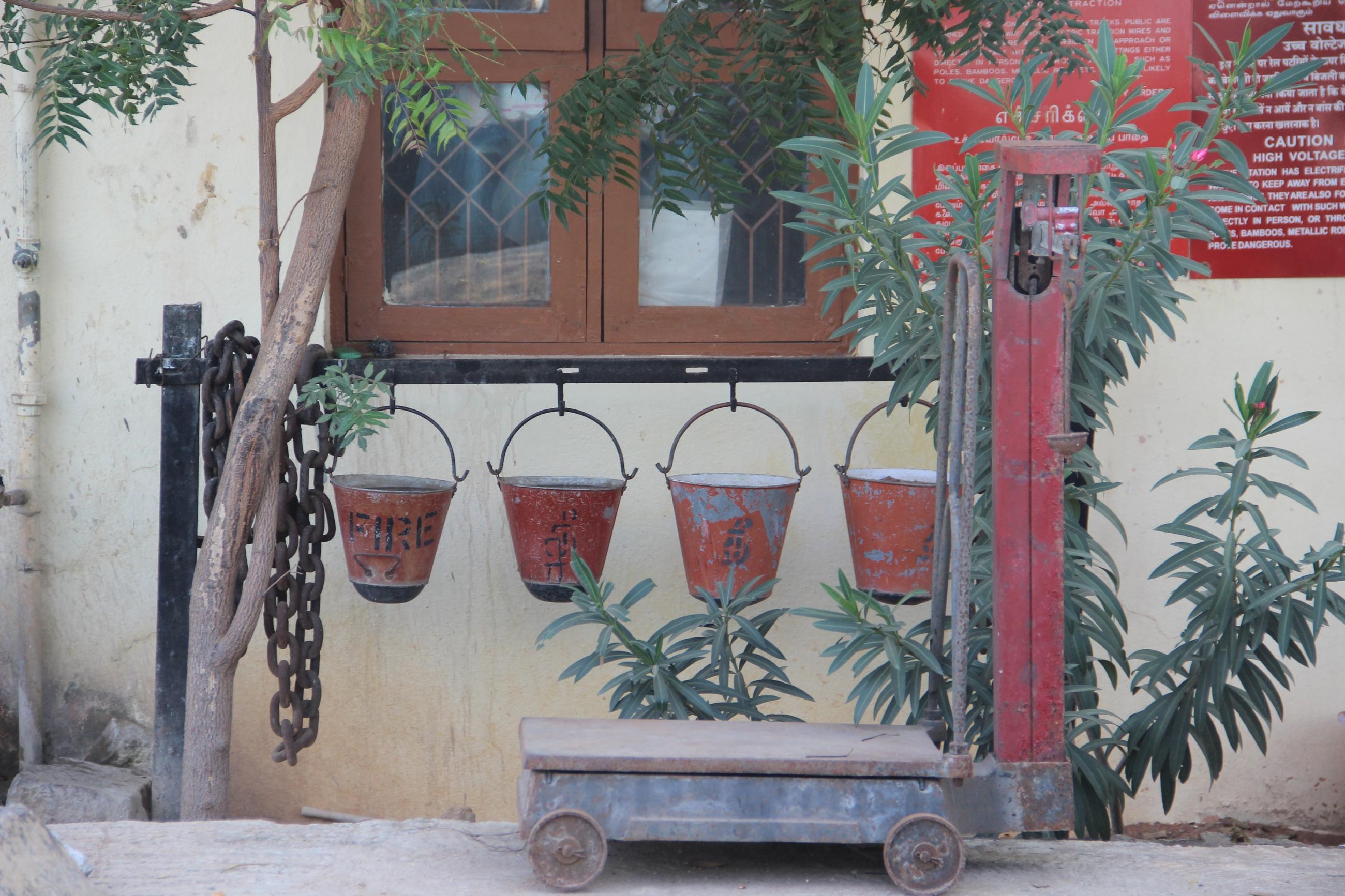 Foto: Eine Löschstation. Vier rote Eimer hängen an einer schwarzen Metallstange. Auf einem der Eimer steht 'Fire'. Im Hintergrund wächst ein Oleander, der seine Äste wie Arme streckt.