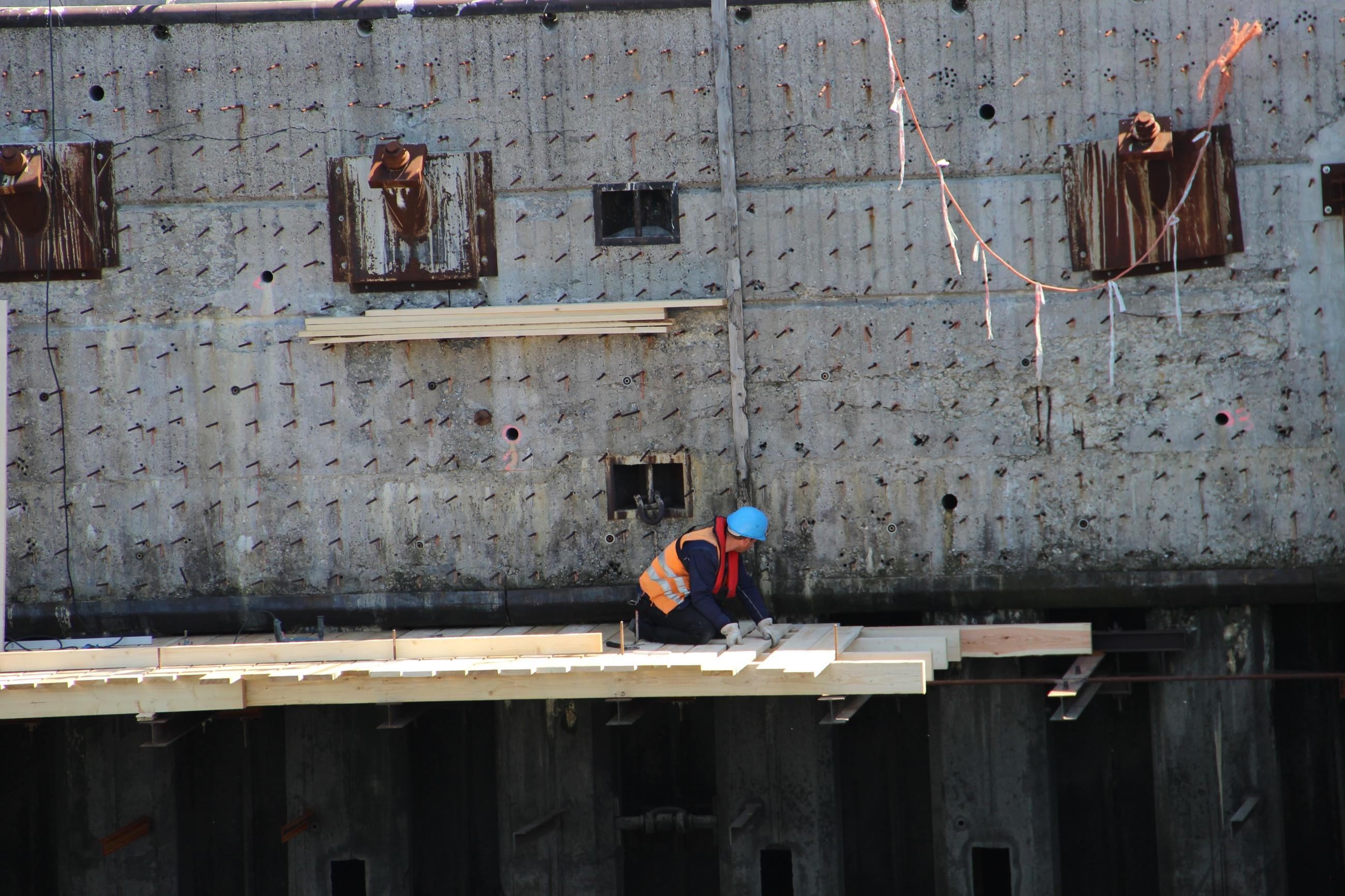Foto: Ein Arbeiter legt einen Steg über einen Abgrund.