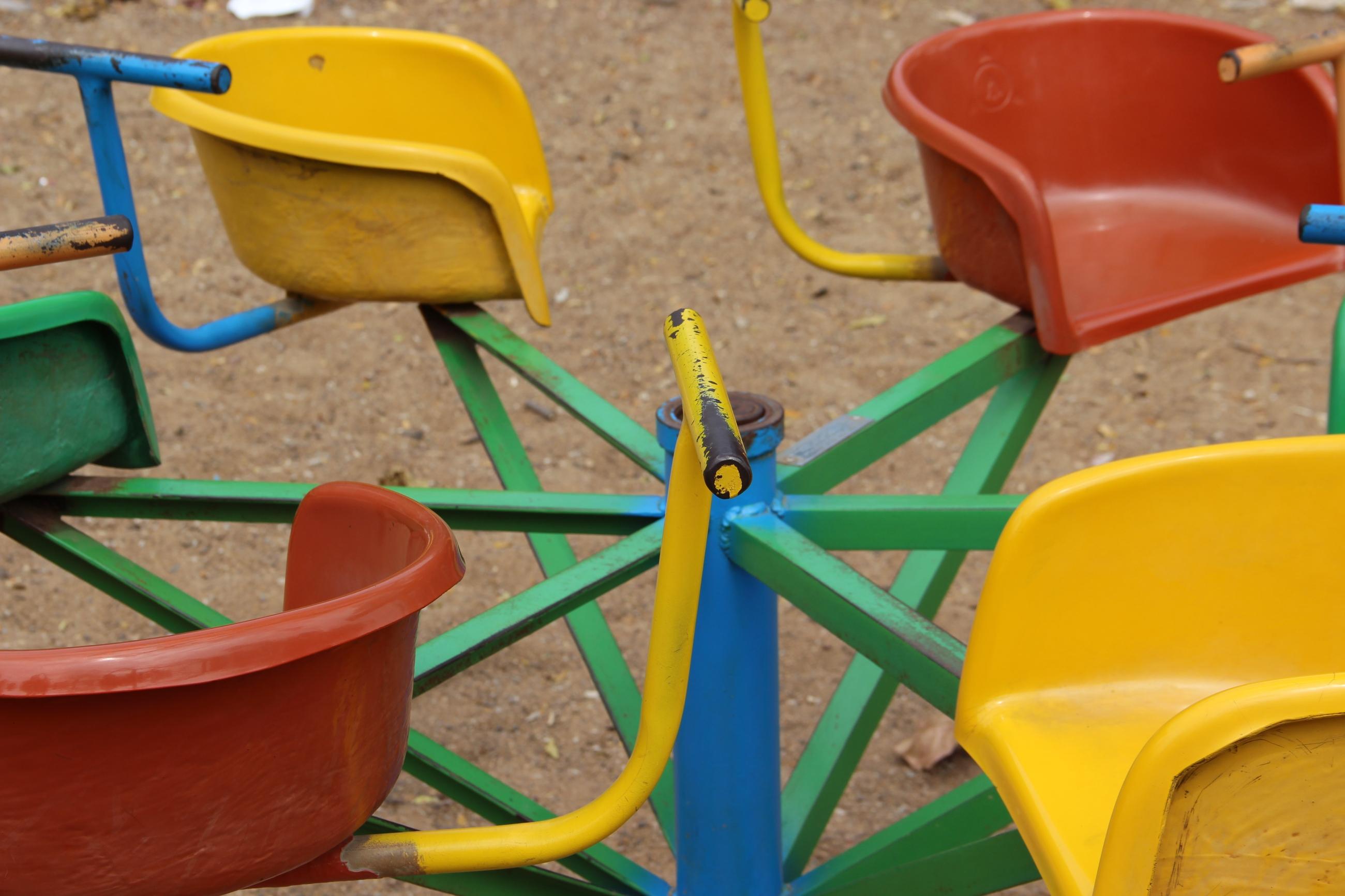 Foto: Kinderkarussel mit gelben und roten Sitzen.