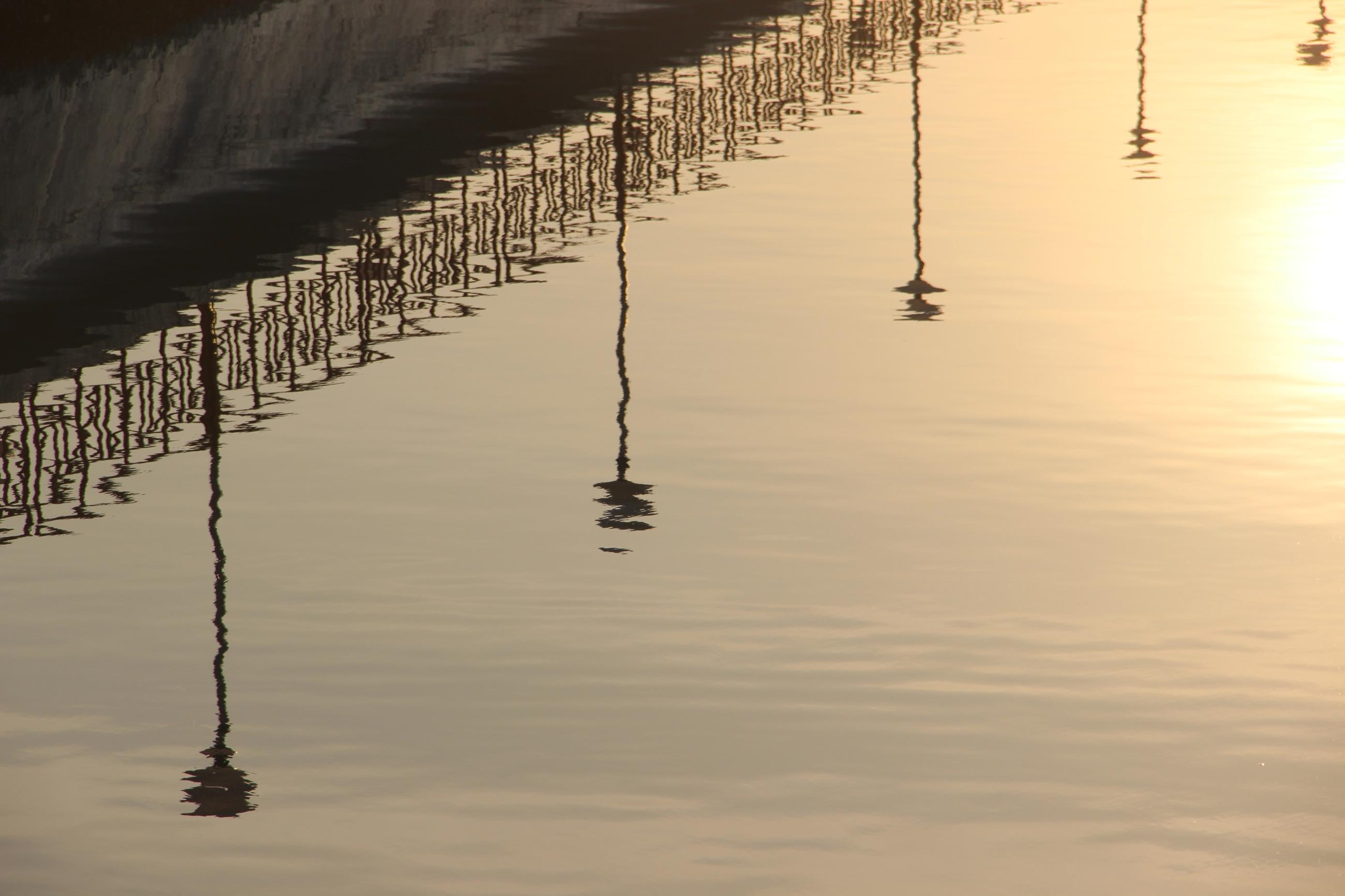 Foto: Eine Promenade spiegelt sich auf ruhigem Meer.