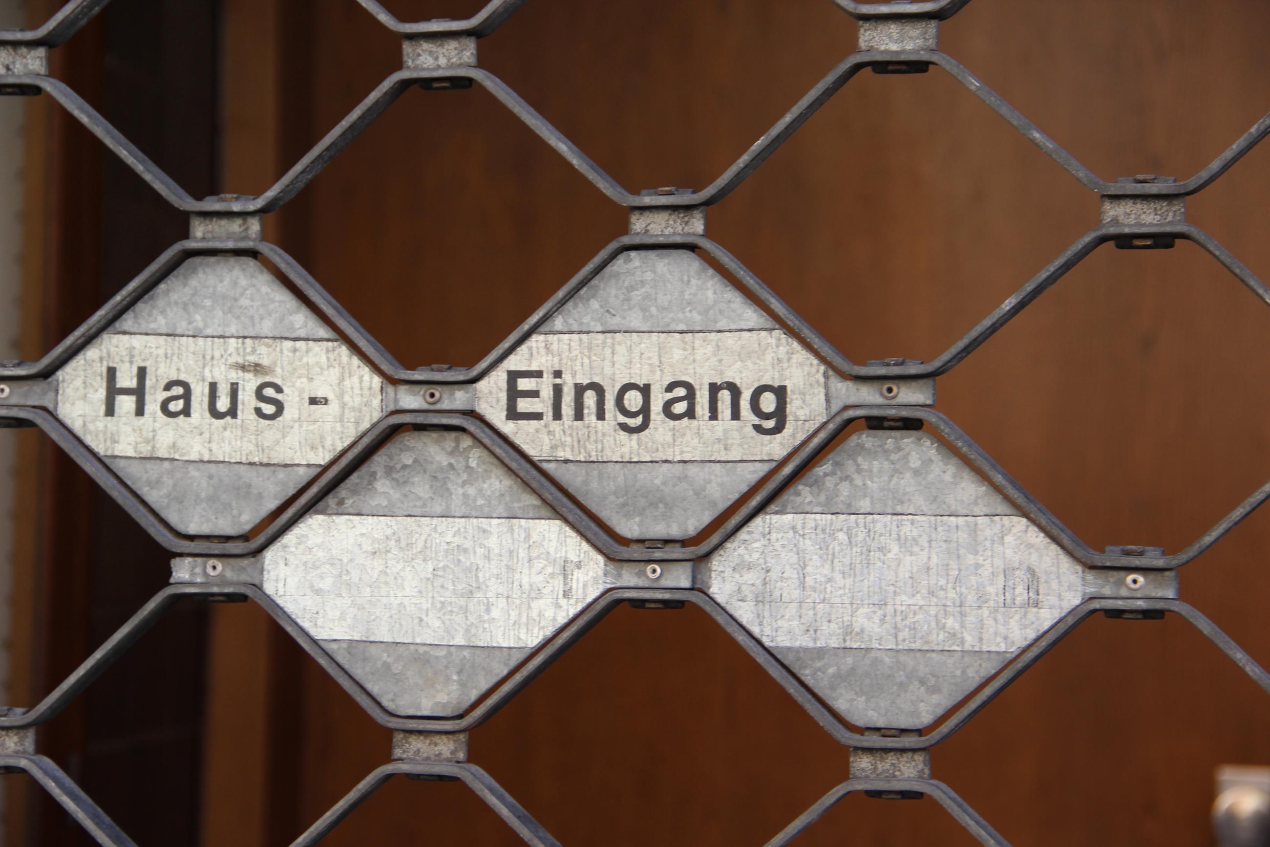 """Foto: Metallgitter mit der Aufschrift: """"Haus-Eingang"""""""