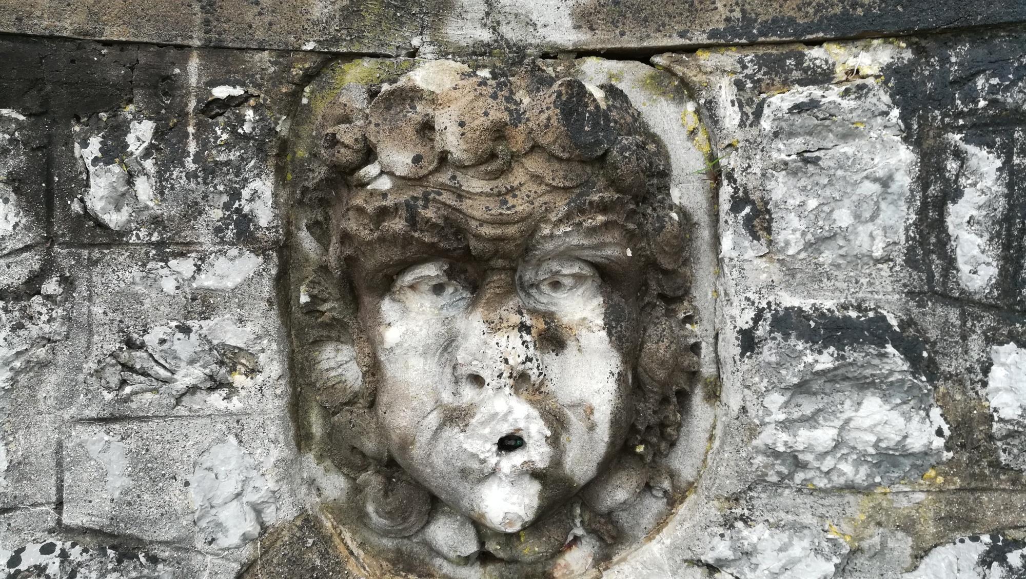 Foto: Verwittertes Gesicht aus Stein.