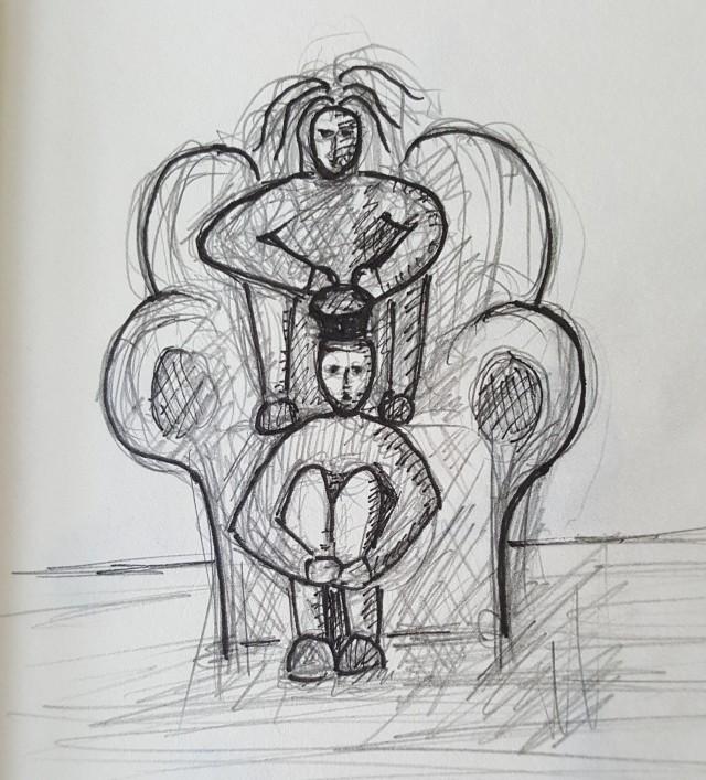 Ein Mann sitzt an ein Sofa gelehnt da. Am Kopf hat er einen runden Gegenstand. Über ihm am Sofa sitzt eine Frau mit struppigem Haar.
